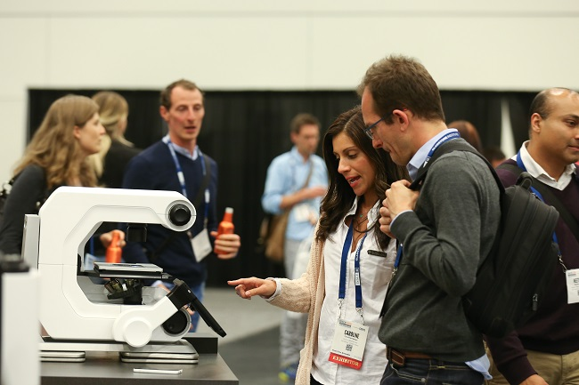 Exhibitor shows equipment to attendee